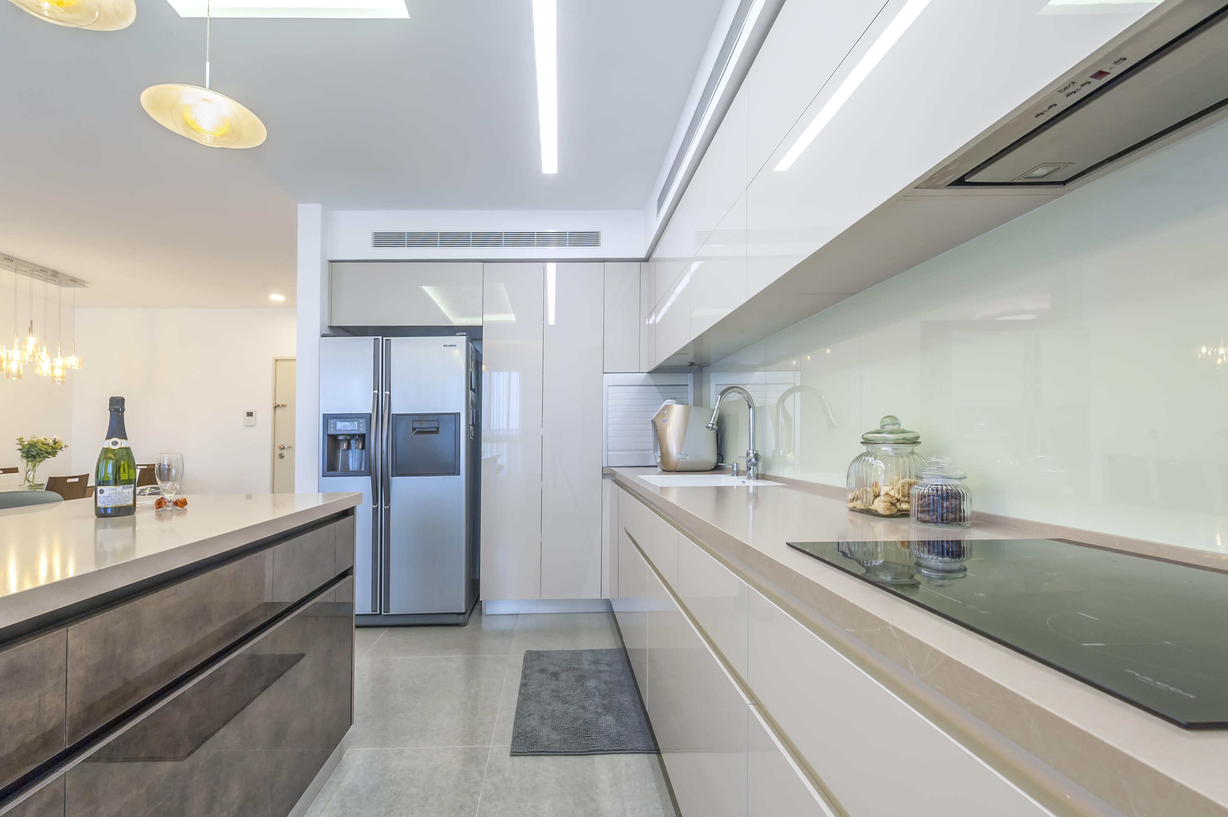 תכנון מטבח מודרני בקווים נקיים שטח אחסון מורחב בחזית המטבח