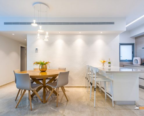 מבט לפינת האוכל והמטבח שולחן מעץ טבעי ובהיר